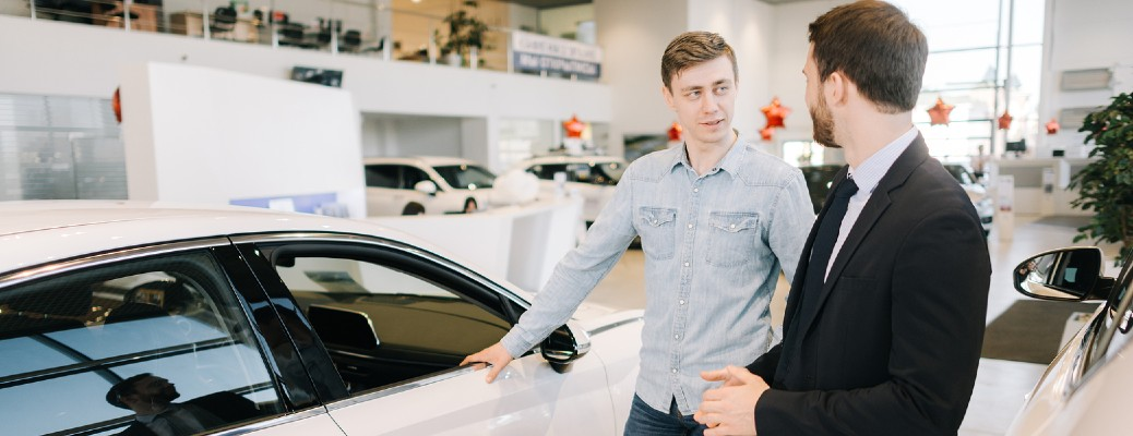Two men talking next to a white car while inside a car dealership