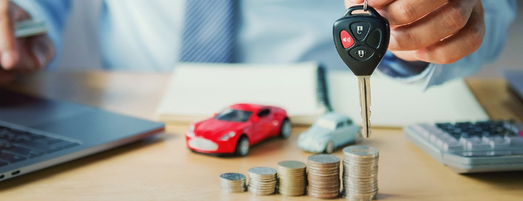 A hand holding up car keys near a desk with a laptop keyboard, plastic red car, coins, and a calculator are resting.