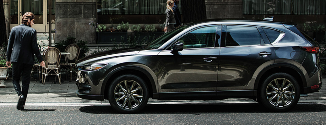 Side view of grey 2020 Mazda CX-5 parked on the street with man standing next to it
