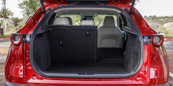 Rear view of red 2020 Mazda CX-30 with liftgate open and one rear seat folded down