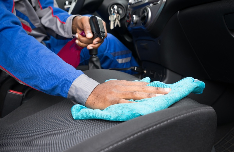 person cleaning the passenger seat inside a vehicle