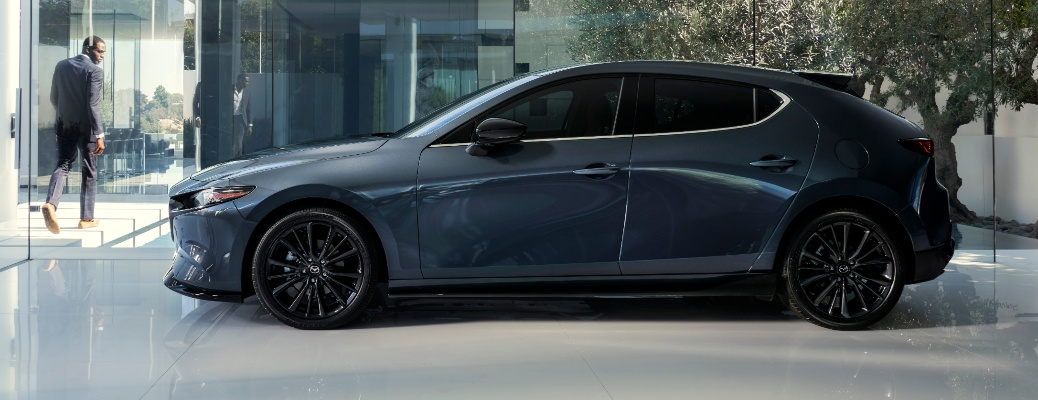 Profile view of the 2021 Mazdda3 2.5-turbo with a man walking away in the background