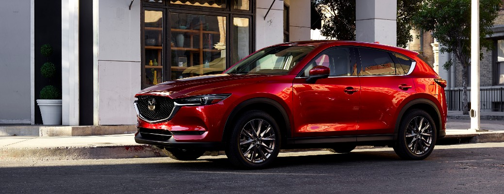 The front and side view of a red 2021 Mazda CX-5 parked on the side of a city street.