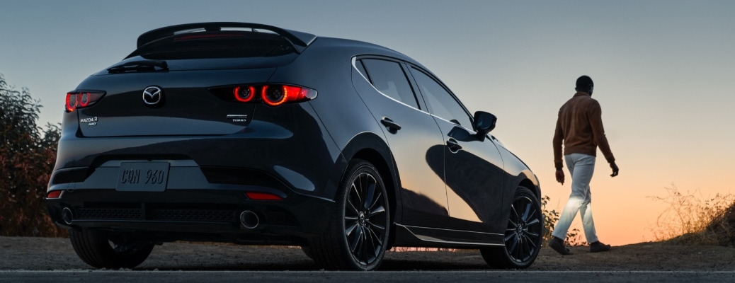 Back end of the 2021 Mazda3 Hatchback and a person walking away