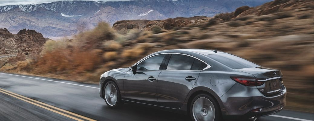 2021 Mazda6 racing through the road surrounded by mountains