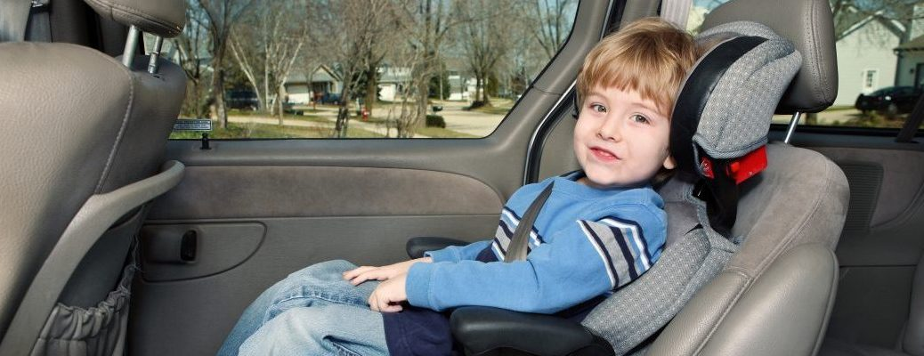 Boy in a booster seat in the back of a van