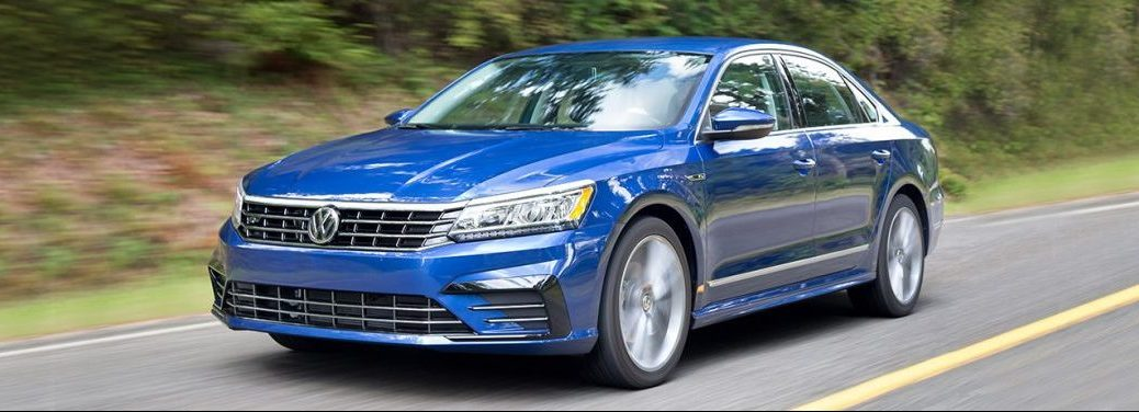 full view of the 2018 vw passat driving in the country by some trees