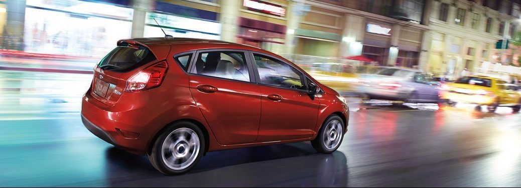 2018 Ford Fiesta in red driving in the city