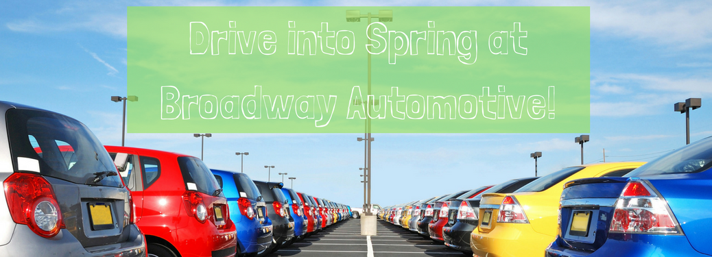 "cars on car dealership lot with text ""drive into spring at broadway automotive"" above it"