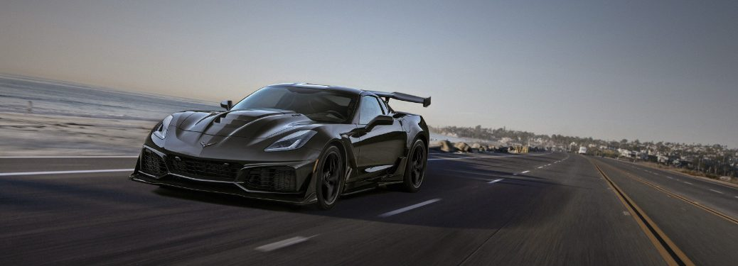 black 2019 chevrolet corvette zr1 driving on empty road next to ocean