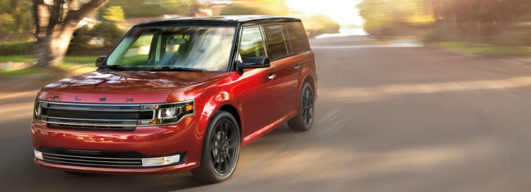 red 2018 ford flex driving down suburban road