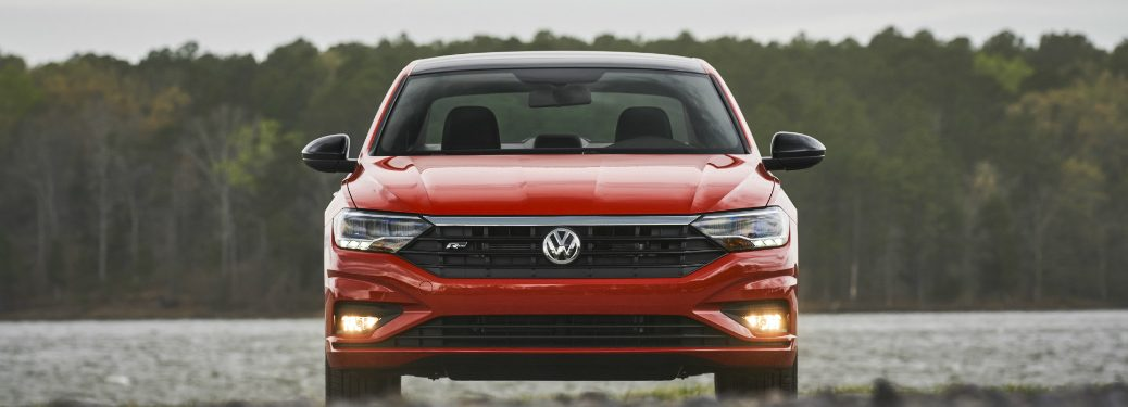 front bumper and grille of orange 2019 volkswagen jetta with a lake and trees behind it