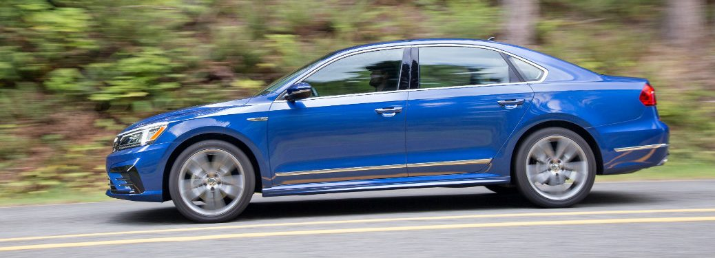 side view of blue 2018 volkswagen passat driving on forest road
