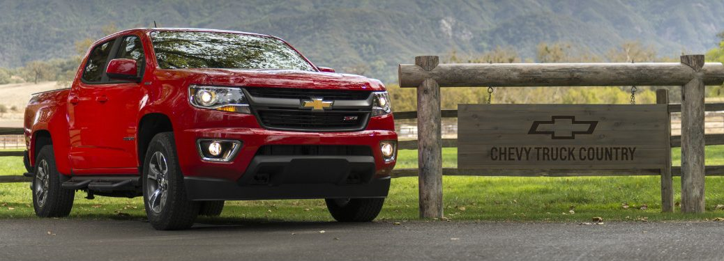 """red 2018 chevy colorado on ranch road next to wooden sign that says """"chevy country"""""""
