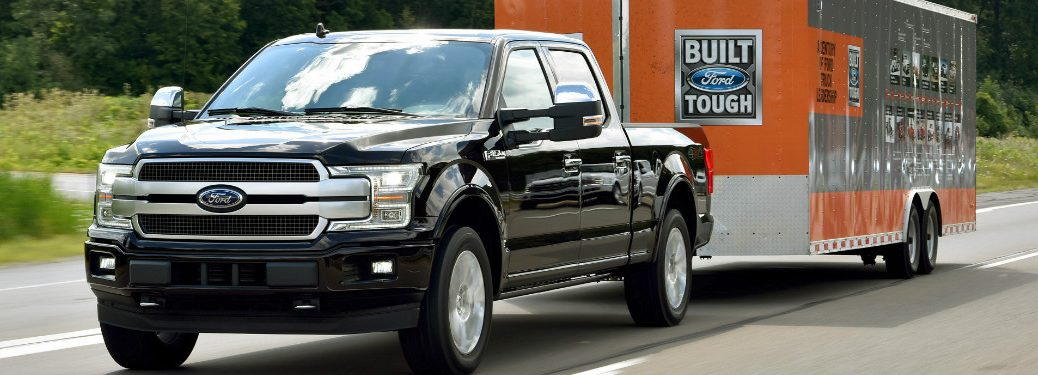 black 2018 ford f-150 towing orange ford trailer on highway