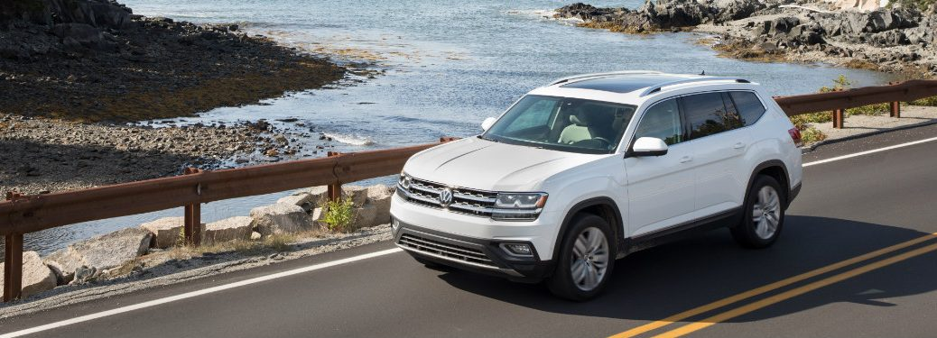 white 2018 volkswagen atlas driving over bridge of lake and rocky beach