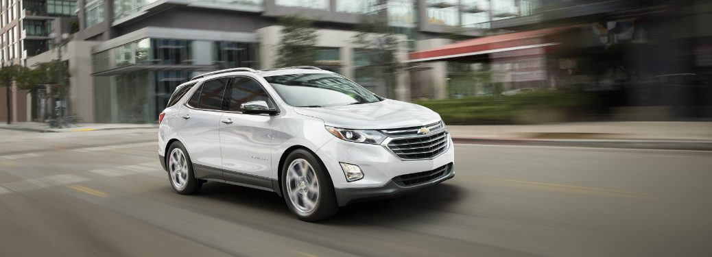 white 2018 chevrolet equinox driving through downtown street