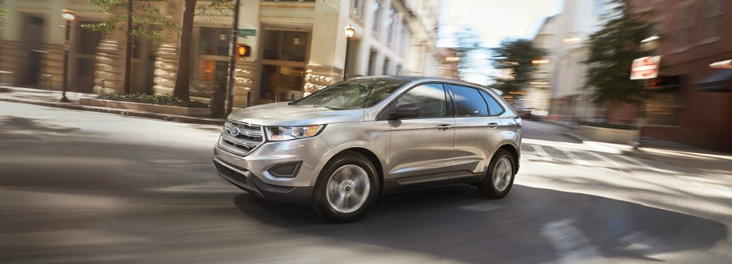 silver 2018 ford edge driving through intersection of city