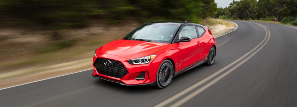 red 2019 hundai veloster driving on empty two-lane road