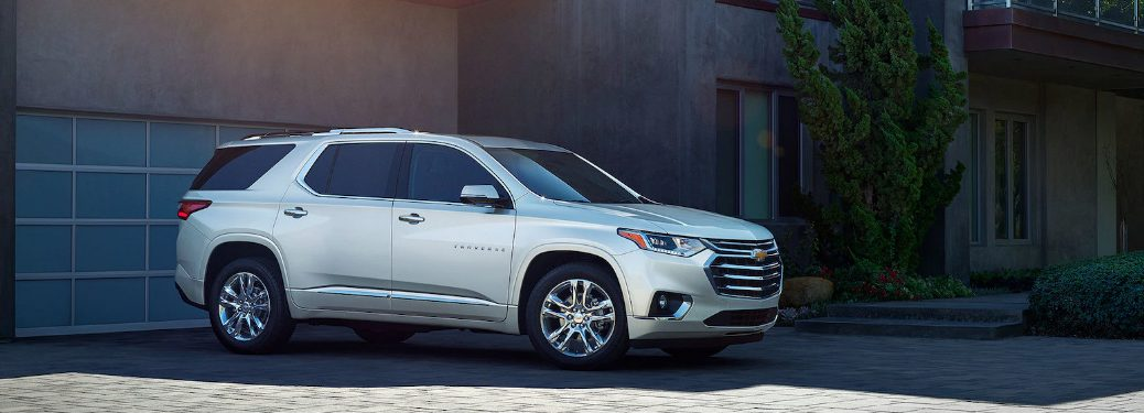 side view of white 2019 chevrolet traverse in driveway of modern home