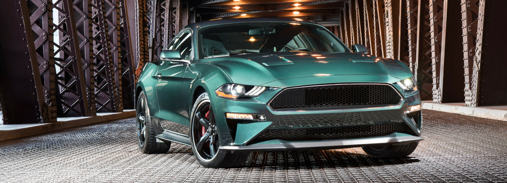 front and side view of green 2019 ford mustang bullitt on bridge