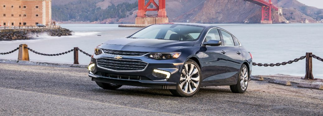 front and side view of blue 2018 chevrolet malibu in front of river