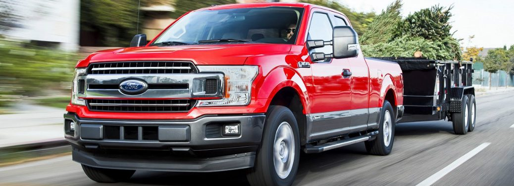 red 2018 ford f-150 power stroke diesel towing trailer on road