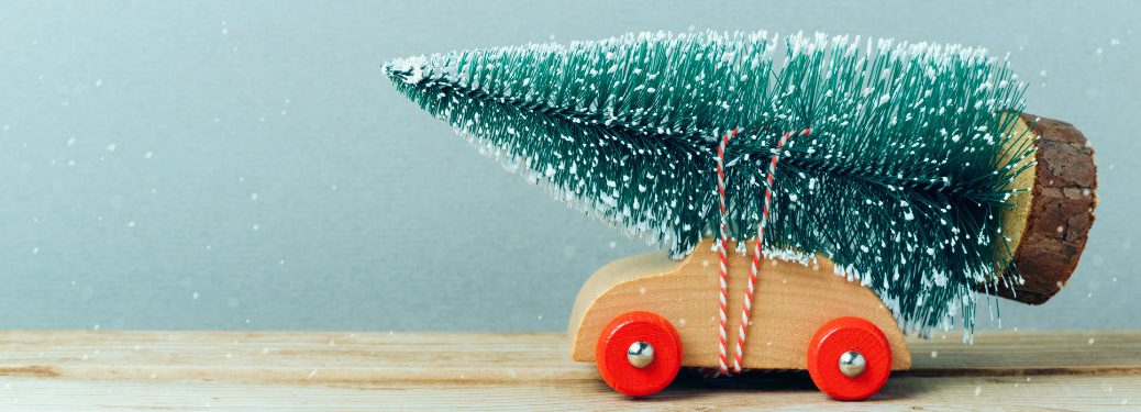 wooden toy car with toy christmas tree strapped to its hood