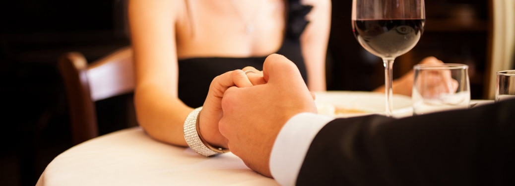 man and woman holding hands at dinner in fine dining restaurant