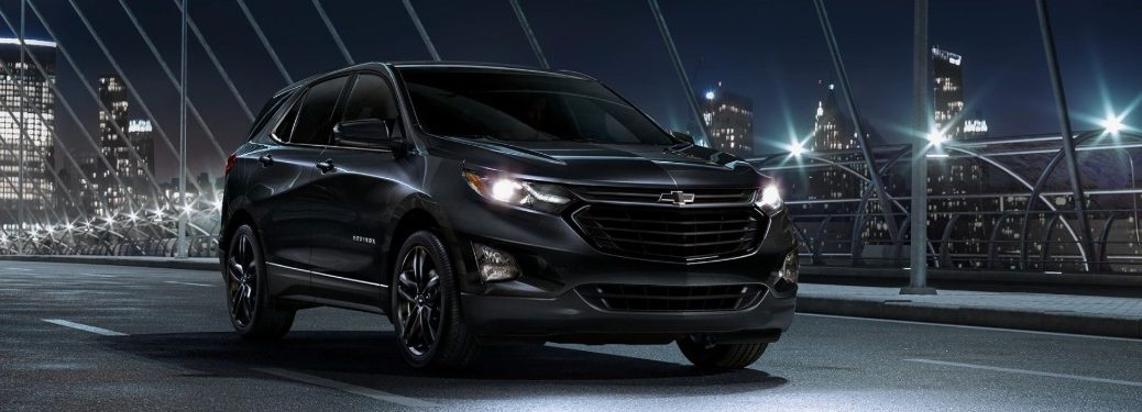 Front passenger angle of a 2020 Chevy Equinox with Midnight Edition driving down a city road at night