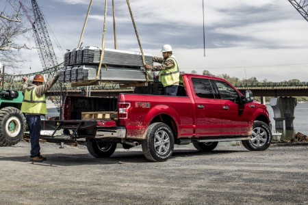 Rear passenger angle of a red 2020 Ford F-150 with workers lowering steel beams into the truck bed