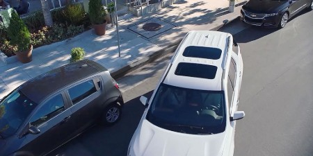 Front aerial angle of a white 2020 Chevrolet Traverse parallel parking on a street
