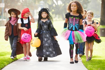 Group of kids in Halloween costumes trick or treating