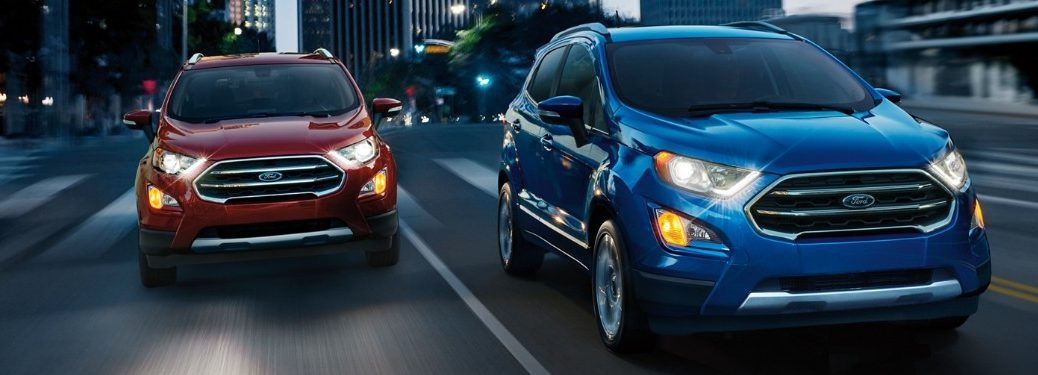 Front passenger angle of a blue 2019 Ford EcoSport driving next to a red 2019 Ford EcoSport in the city