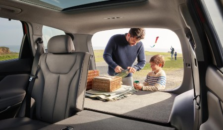 The interior of the 2020 Hyundai Santa Fe with the rear seats down and a father and son standing at the rear with the liftgate open