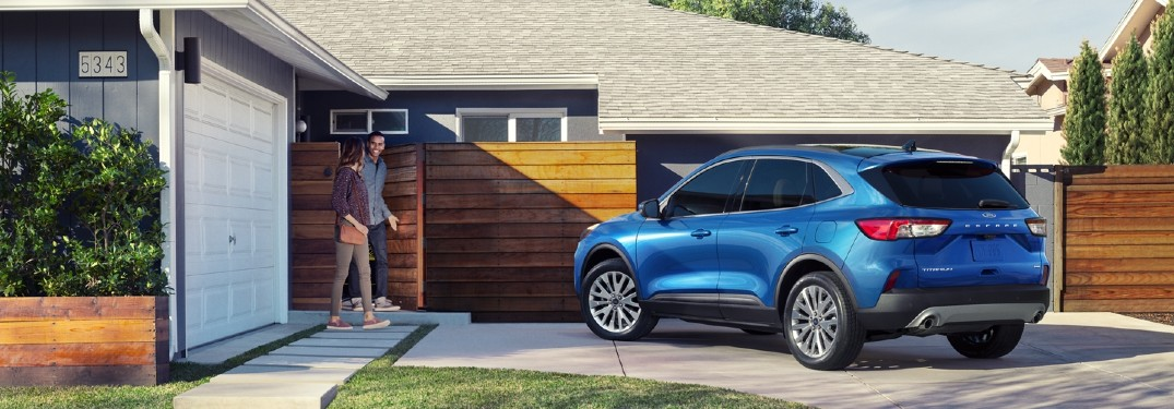 Rear driver angle of a blue 2020 Ford Escape parked in a driveway with a couple walking towards it