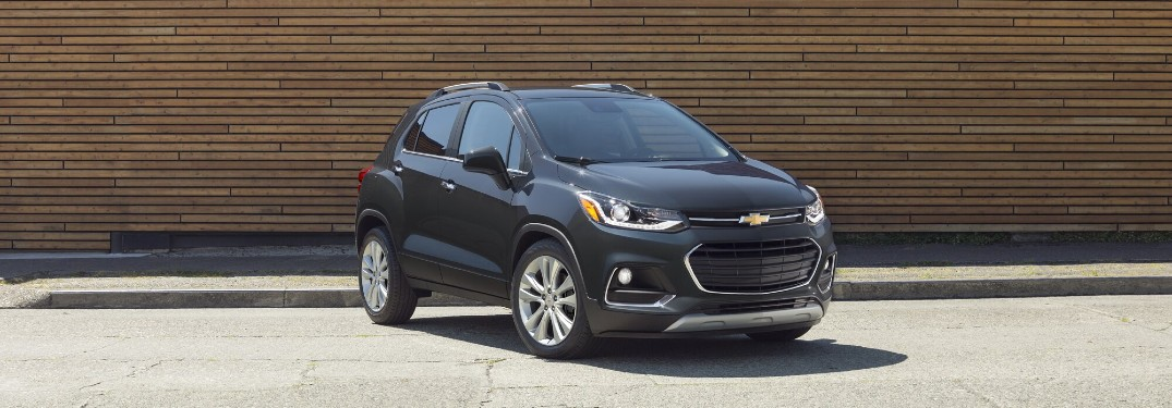 Front passenger angle of a black 2020 Chevrolet Trax parked in front of a building