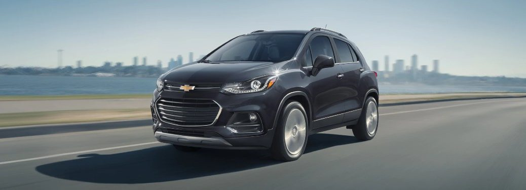 Front driver angle of a black 2020 Chevrolet Trax driving by a lake with a city in the background