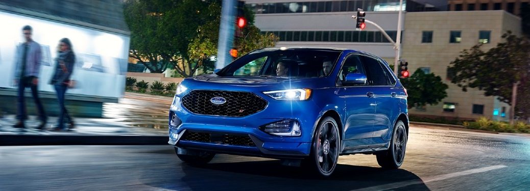 Front driver angle of a blue 2020 Ford Edge driving at night