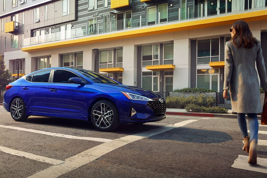 Front passenger angle of a blue 2020 Hyundai Elantra on the road with a woman crossing the street in front