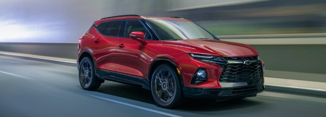 Front passenger angle of a red 2020 Chevrolet Blazer driving on a road