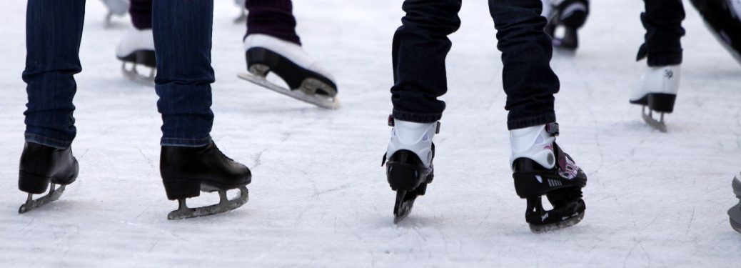 Close up of the skates of people ice skating