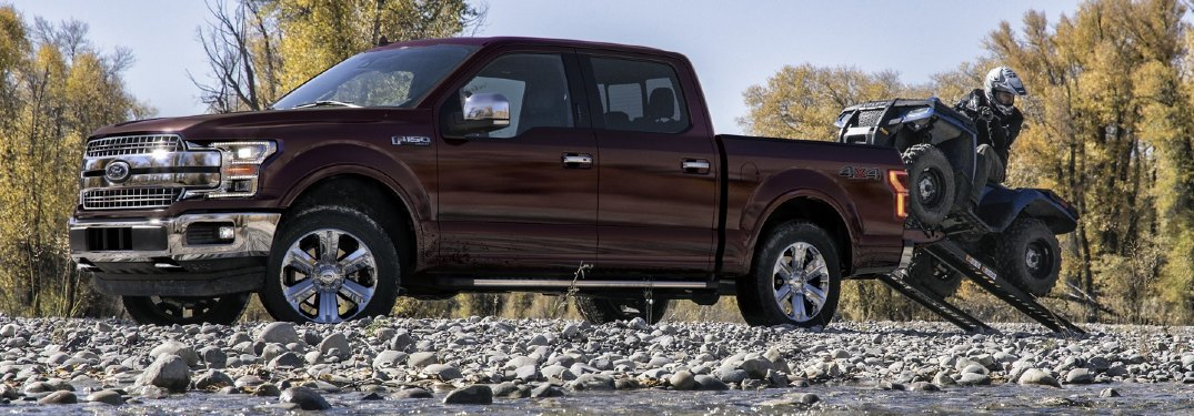 Driver angle of a dark red 2020 Ford F-150 with a man driving a 4-wheeler out of the payload