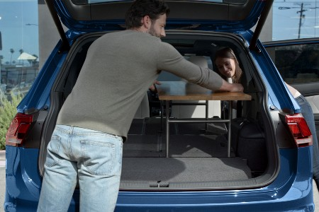 Rear angle of a couple placing a table inside a blue 2020 Volkswagen Tiguan