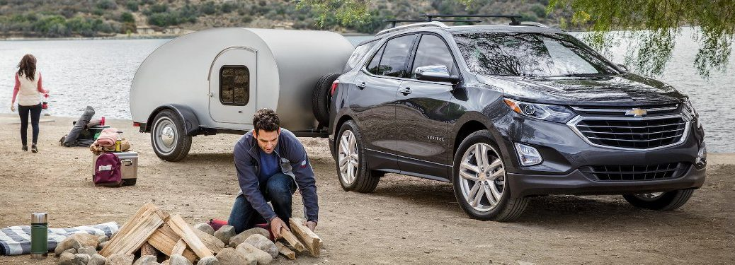Grey 2020 Chevy Equinox hitched to a trailer by a lake with a couple preparing to camp