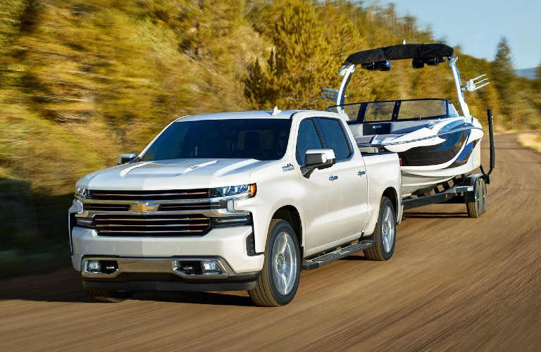 Front driver angle of a white 2020 Chevy Silverado 1500 towing a boat