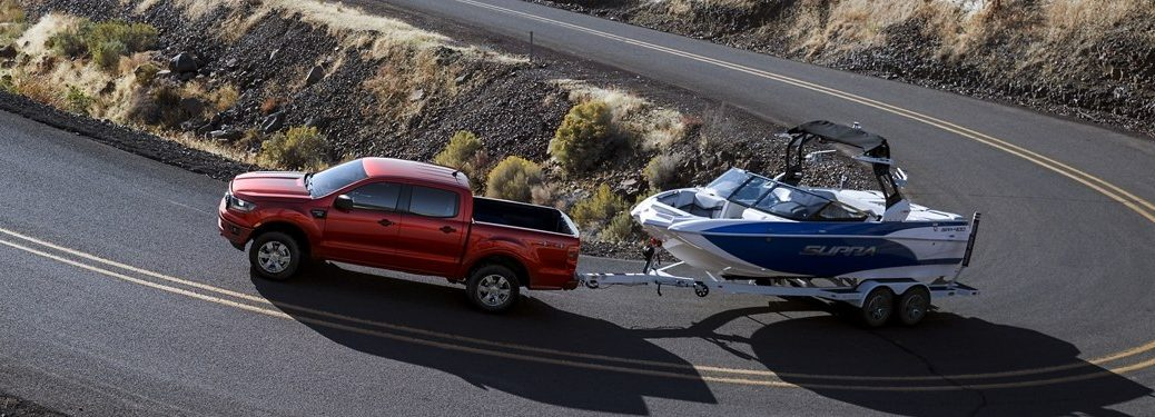 Driver angle of a red 2020 Ford Ranger towing a boat