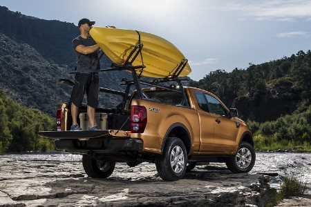 Rear angle of a man getting a kayak off the roof of an orange 2020 Ford Ranger