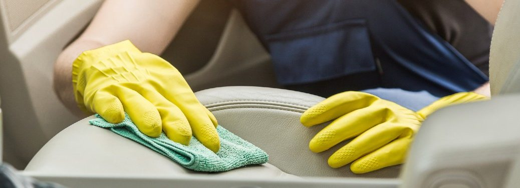 Close up of a worker cleaning a car seat