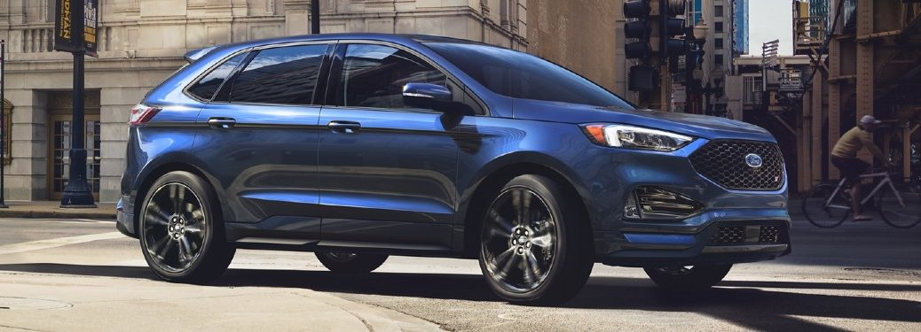 Front passenger angle of a blue 2020 Ford Edge driving in a city